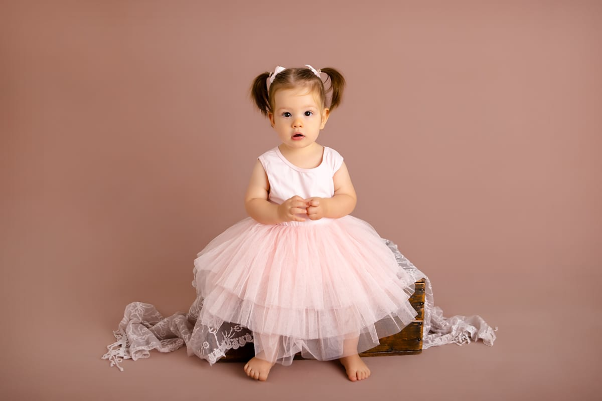 gorgeous baby girl sitting on box posing beautifully during her cake smash photo session