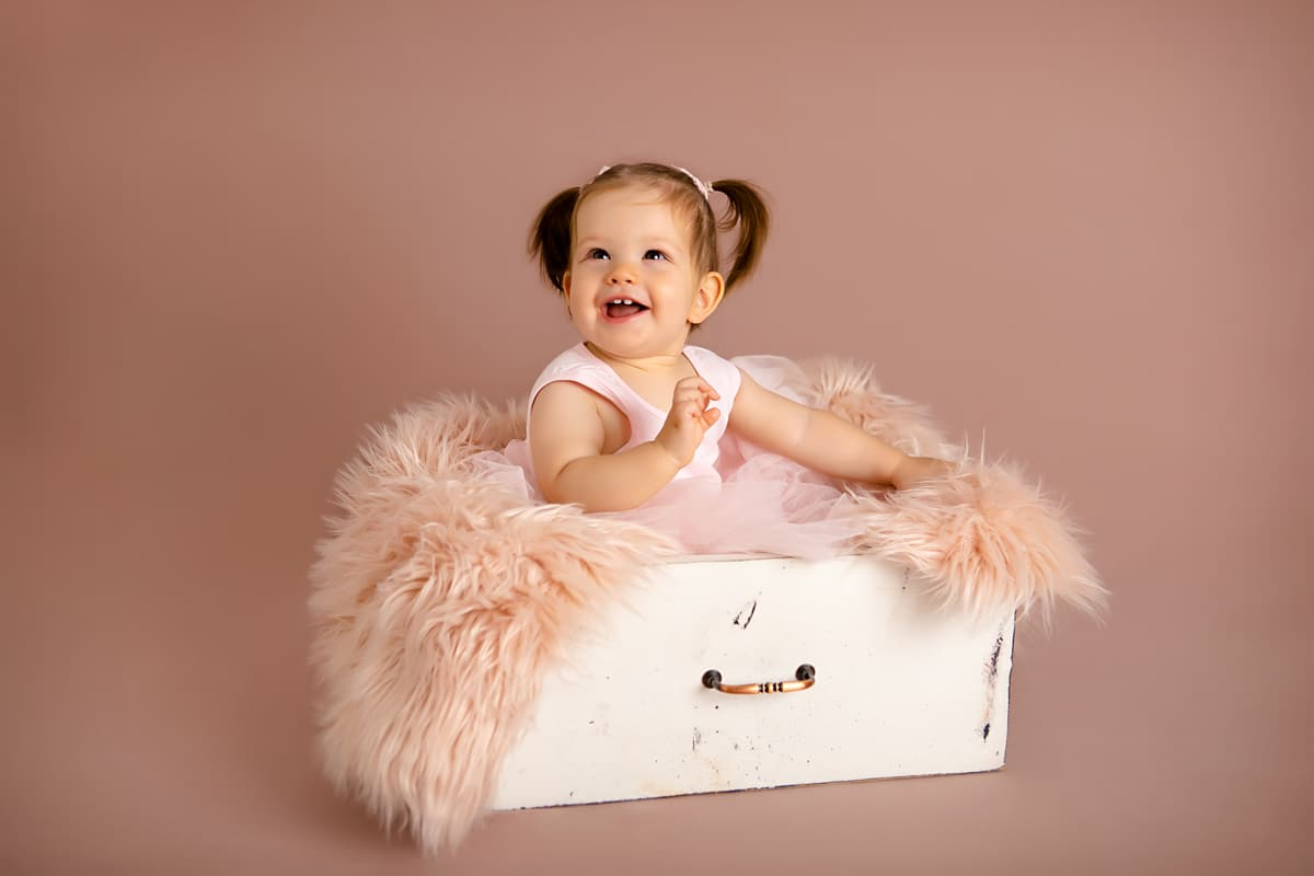 Baby girl at the age of one sitting in a drawer with a fluffy rug laughing