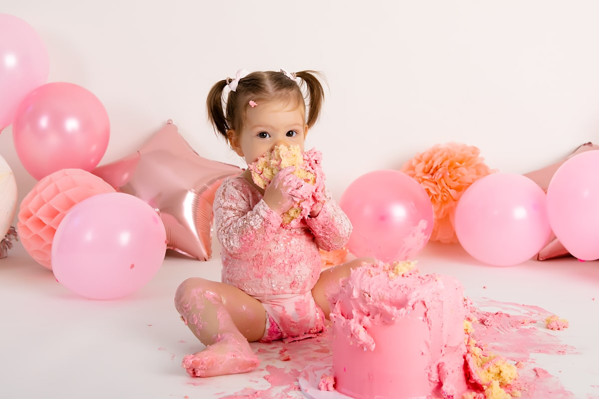 One year old baby girl eating a big chunk of cake during her Cake Smash Photography North Coogee